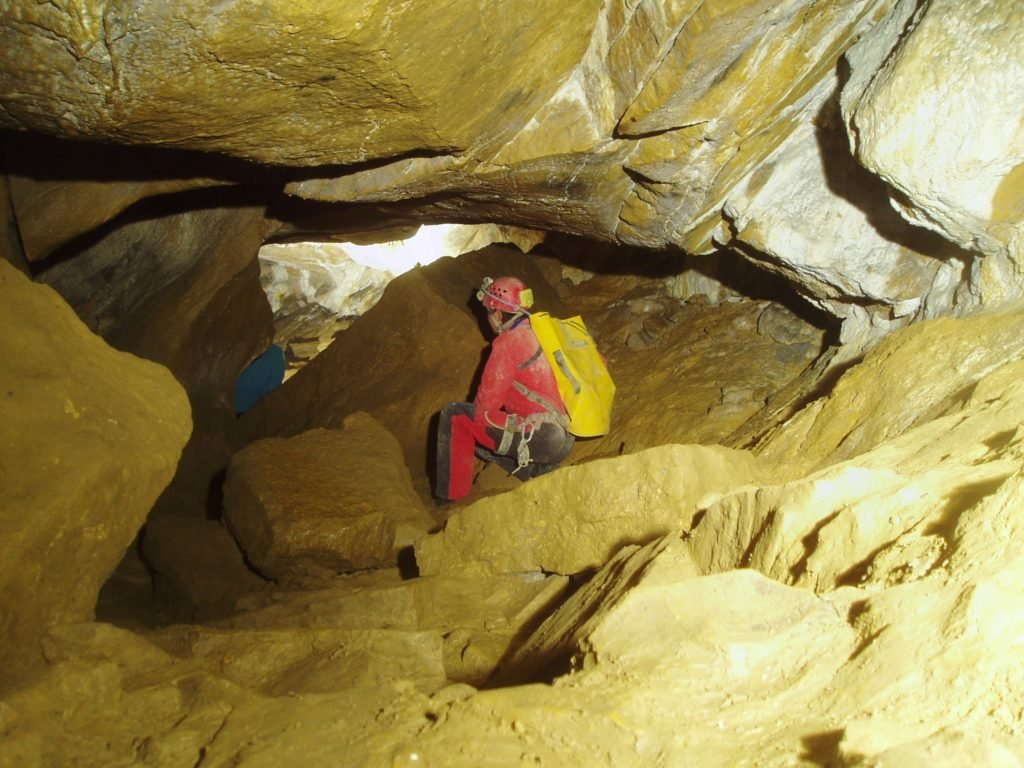 Passage entre blocs de roches à la grotte de Jujurieux, Ain. Comment s'habiller pour une sortie spéléologie ? Vous pouvez voir le pratiquant parfaitement équiper.